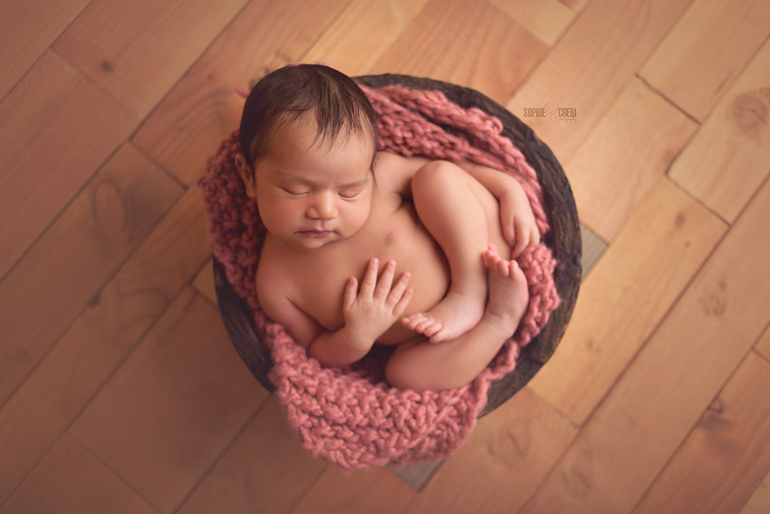 Newborn girl in round wooden bowl with dark pink layering blanket during her infant photo shoot in San Diego