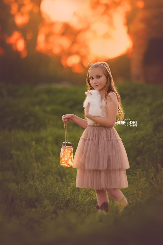 Girl holds a mason jar lantern and a bunny for a magical sunset photo session