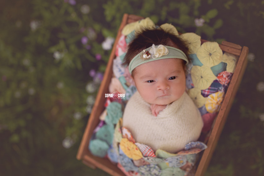 Newborn girl on a colorful quilt during her outdoor newborn photography session in San Diego