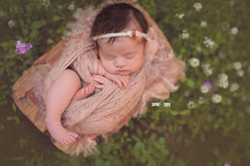 Newborn girl in pale pink wrap outside in nature for outdoor baby newborn photos