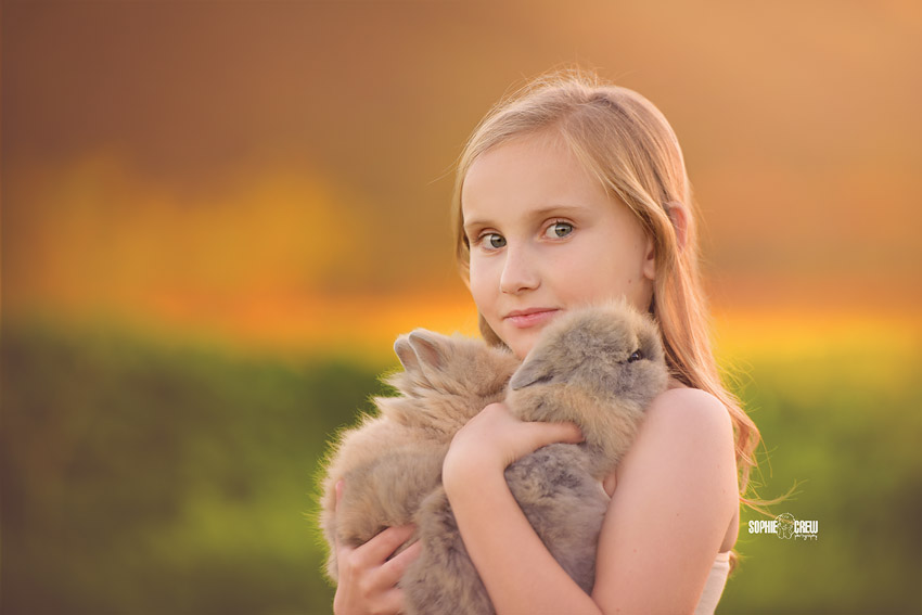 Little girl holding two live bunnies for San Diego photographer