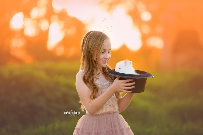 Girl holds a magician's hat with a live bunny