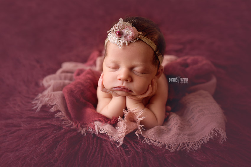 newborn girl in burgundy color doing froggy pose for newborn session in San Diego