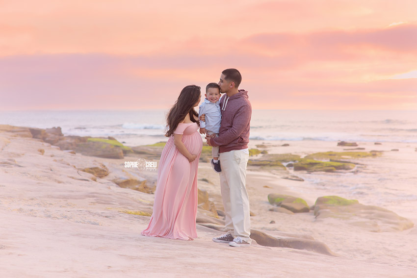 Expectant couple hold toddler son at Southern California beach for photography session with Sophie Crew Photography