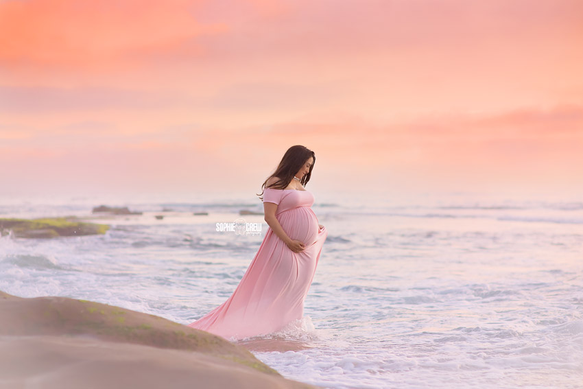 Pregnant mother stands in ocean water at beach holding her belly in pink maternity gown