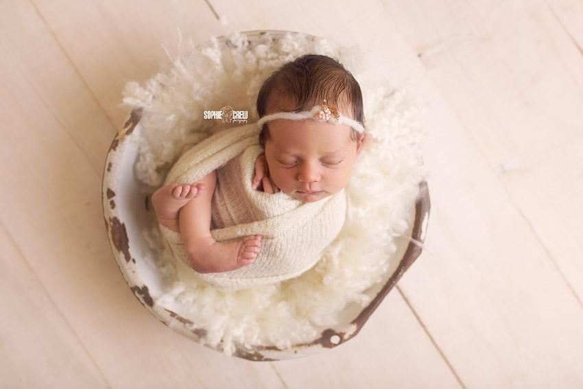 Newborn girl in white bowl with DIY newborn fluff in white
