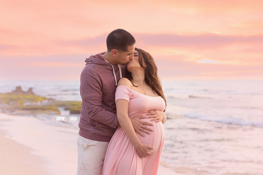 Couple expecting newborn pose at Windansea Beach in San Diego