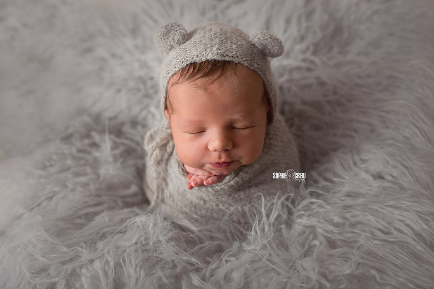 Professional newborn photographer Sophie Crew Photography poses a newborn safely for the potato sack pose how to