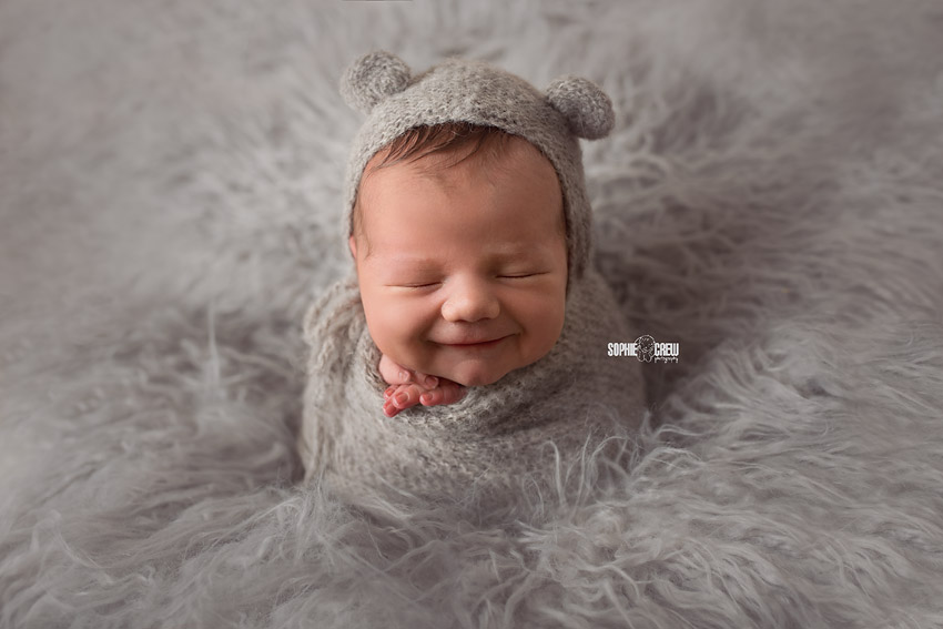 Newborn smiling as he is posed for his potato sack newborn pose