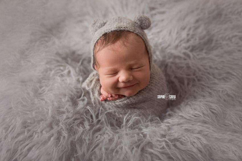 Newborn potato sack pose in gray bonnet and gray fur layer