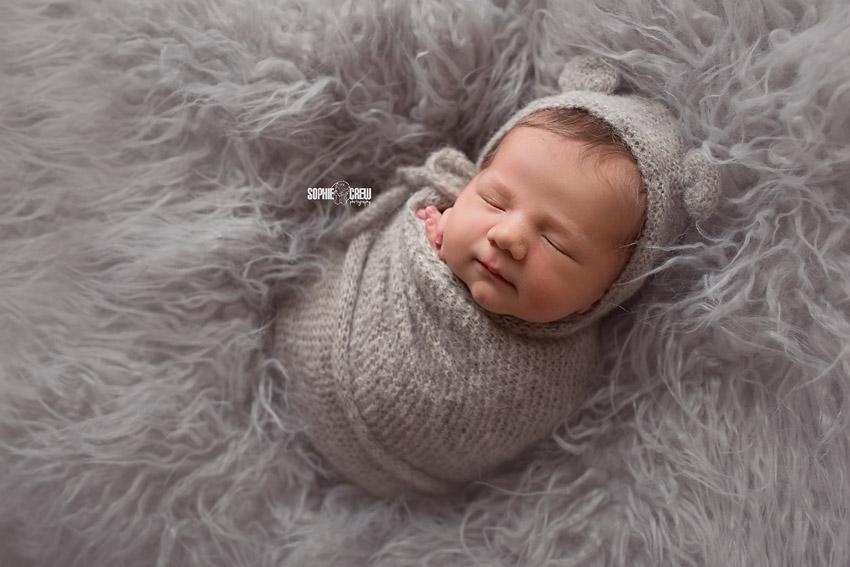 Newborn boy bundled in gray tones with gray bear bonnet