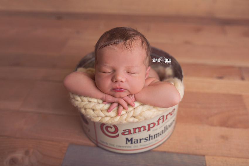 Newborn posed in Campfire Marshmallow vintage antique tin during his sleepy newborn photography session in San Diego, CA