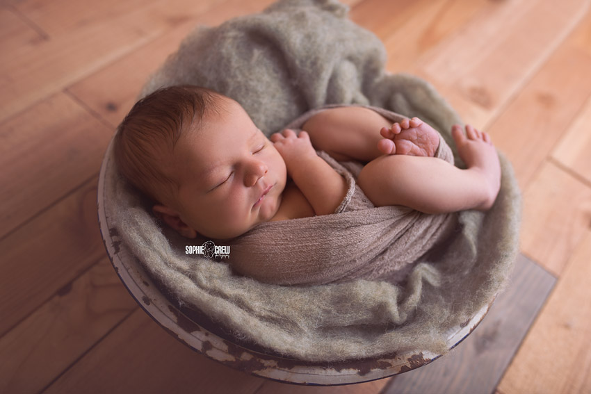 Infant boy in a white bowl with green and brown colors San Diego Newborn Baby Photography