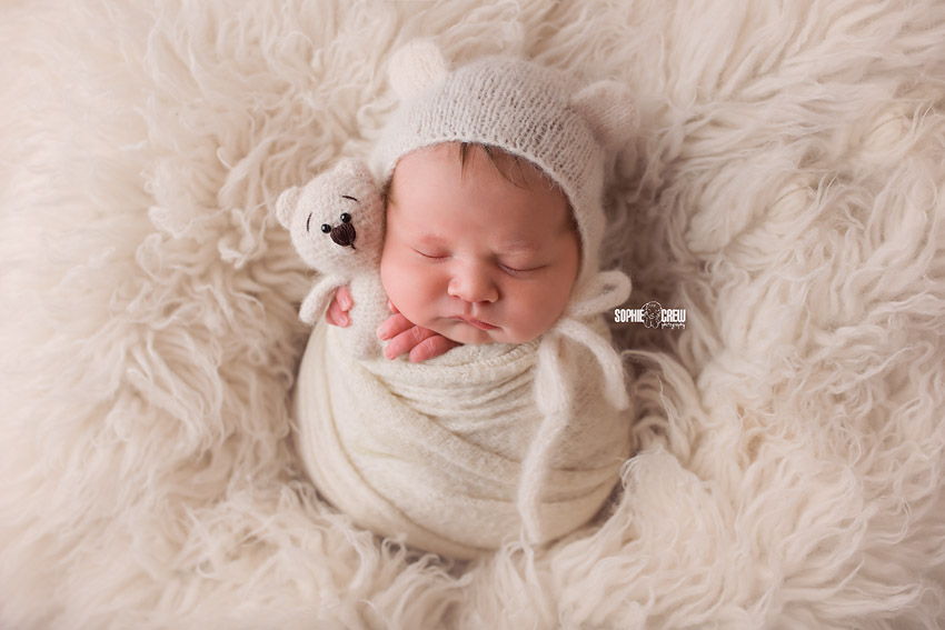 Newborn girl poses in the potato sack pose with a white teddy bear, swaddled tight with a white knit wrap on a white flokati rug