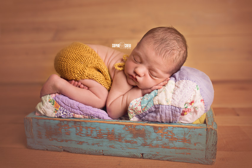 Sophie Crew Photography captures a newborn girl posed in the bum up pose on a colorful quilt in San Diego, CA