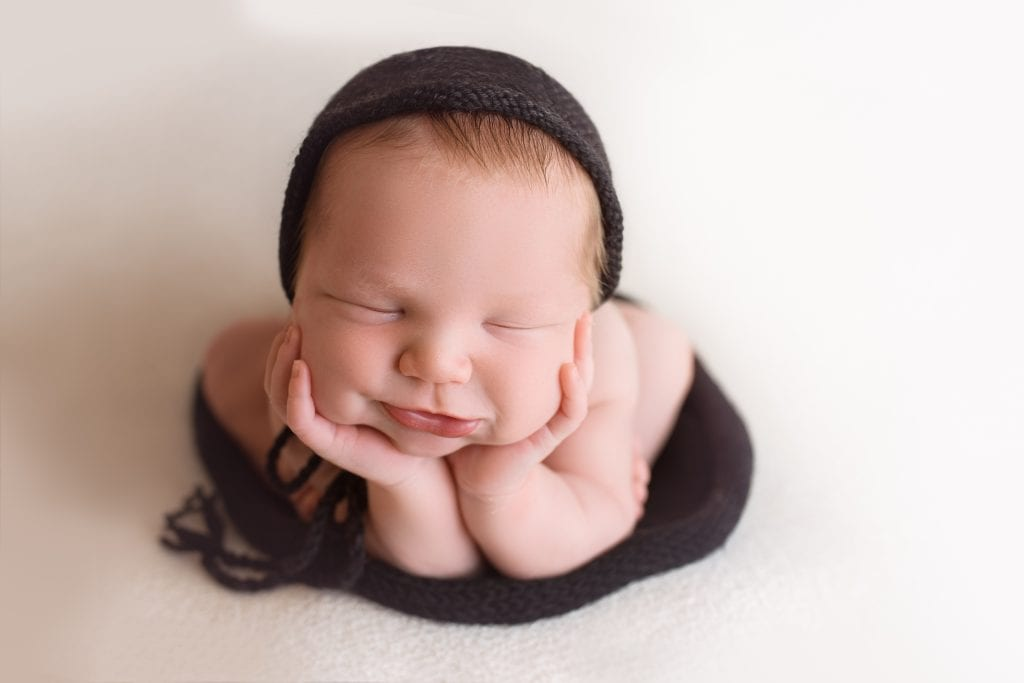 Sophie Crew poses her newborn boy in the froggy pose as he smiles wearing a black knit newborn bonnet and wrap