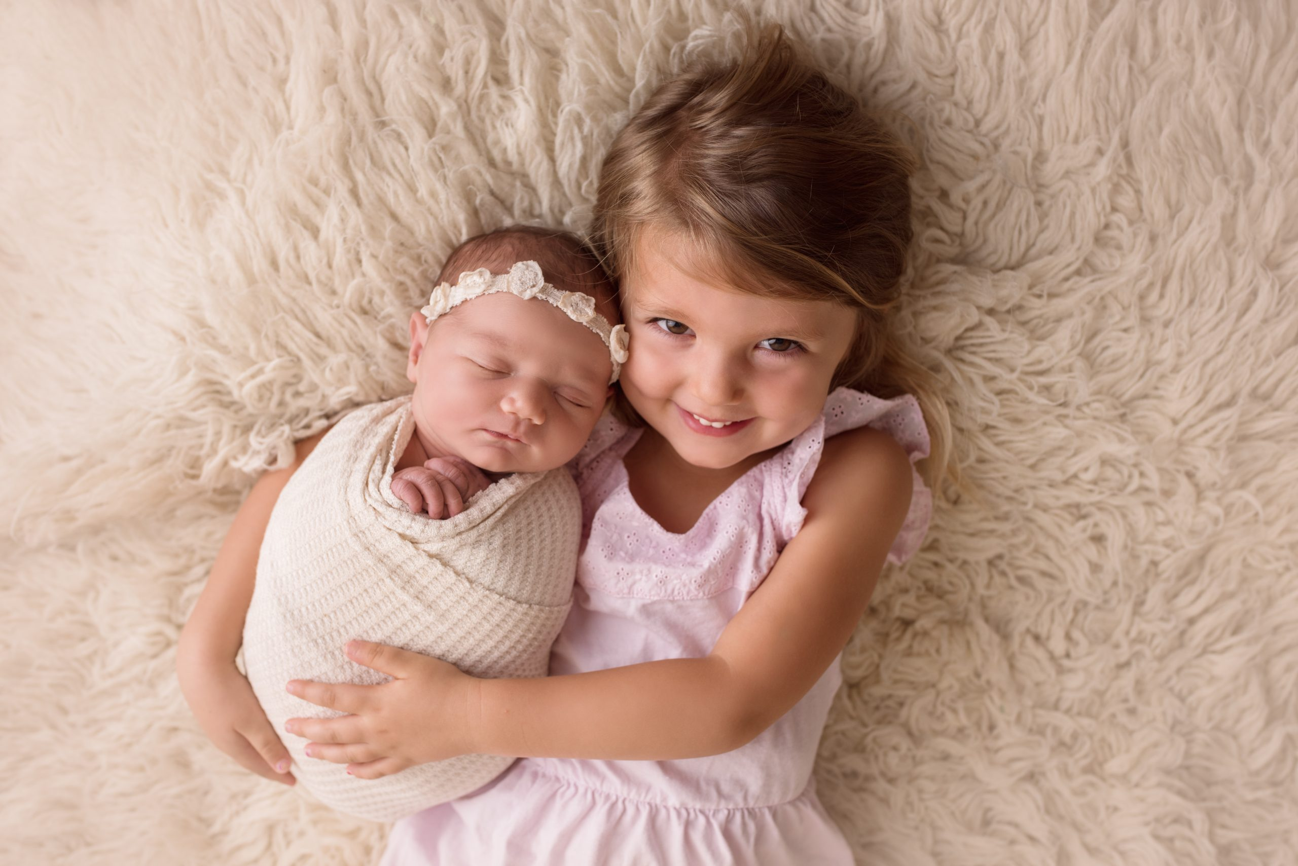 Newborn posed with big sister sibling poses on flokati rug